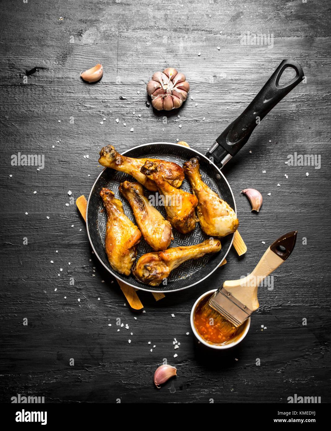Cuisses de poulet frit à l'ail et la sauce. sur un fond en bois noir. Photo Stock