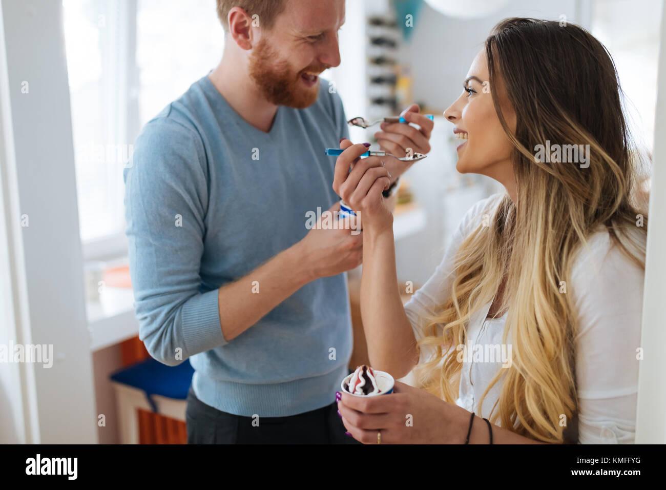 Couple et de rire à la maison tandis que la consommation de crème glacée Photo Stock