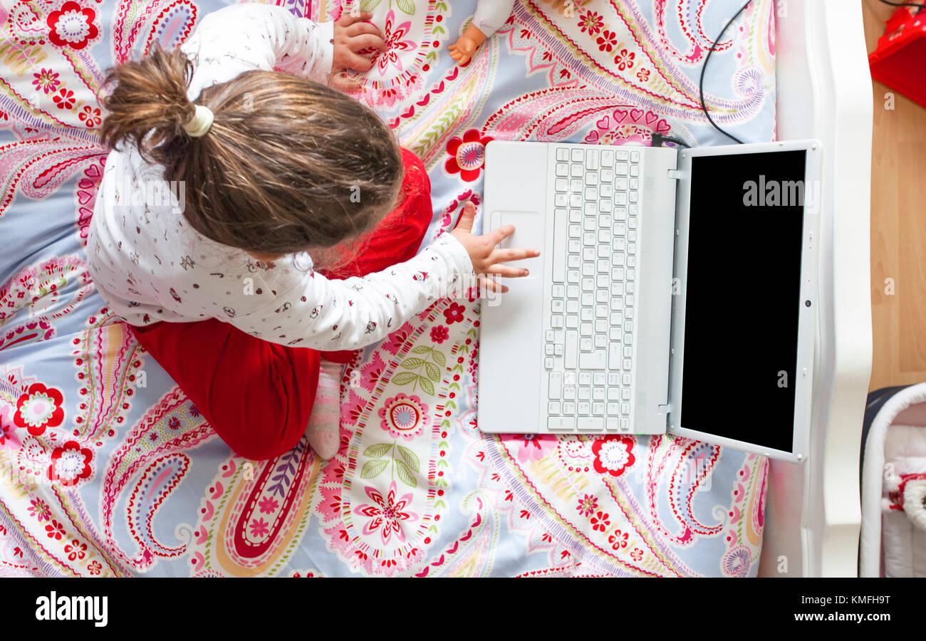 Petite fille assise dans le lit et jouer à des jeux en ligne dans sa chambre à coucher. high angle view Photo Stock