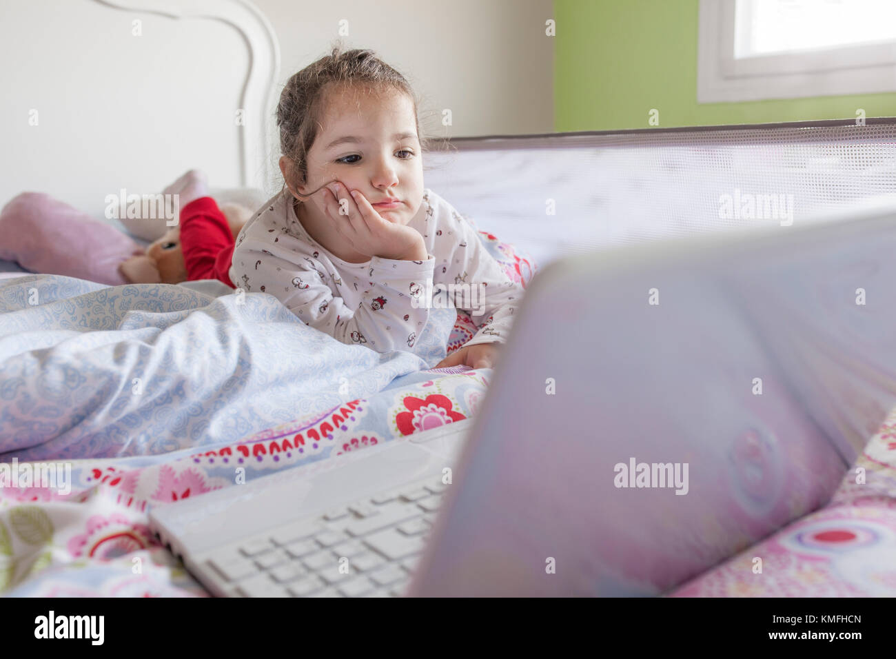 Petite fille au lit et regarder les dessins animés avec un ordinateur portable dans sa chambre. Elle a l'air Photo Stock