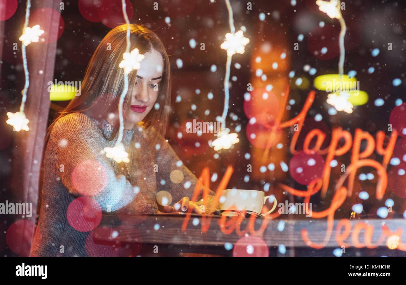 Belle Jeune femme assise dans un café, boire du café. Effet de neige magique. Noël, Bonne Année, Photo Stock