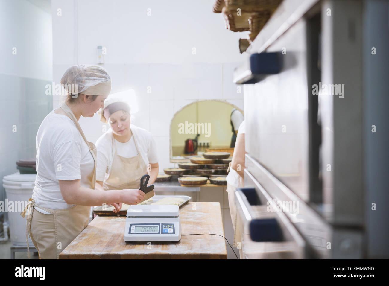 Les cuisiniers travaillent dans le sourire bakery Photo Stock