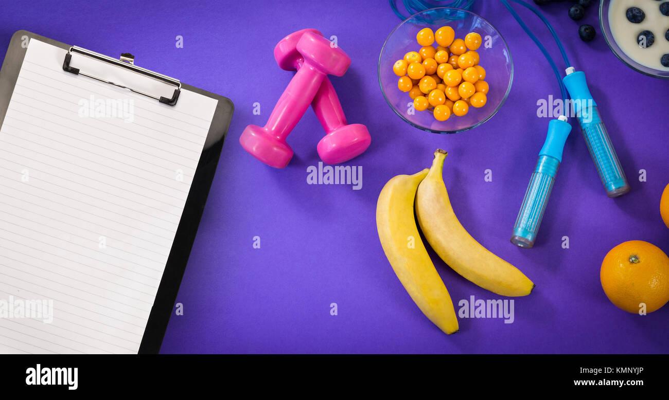 Le bloc-notes noir contre de la nourriture avec l'équipement d'exercice contre fond violet Photo Stock