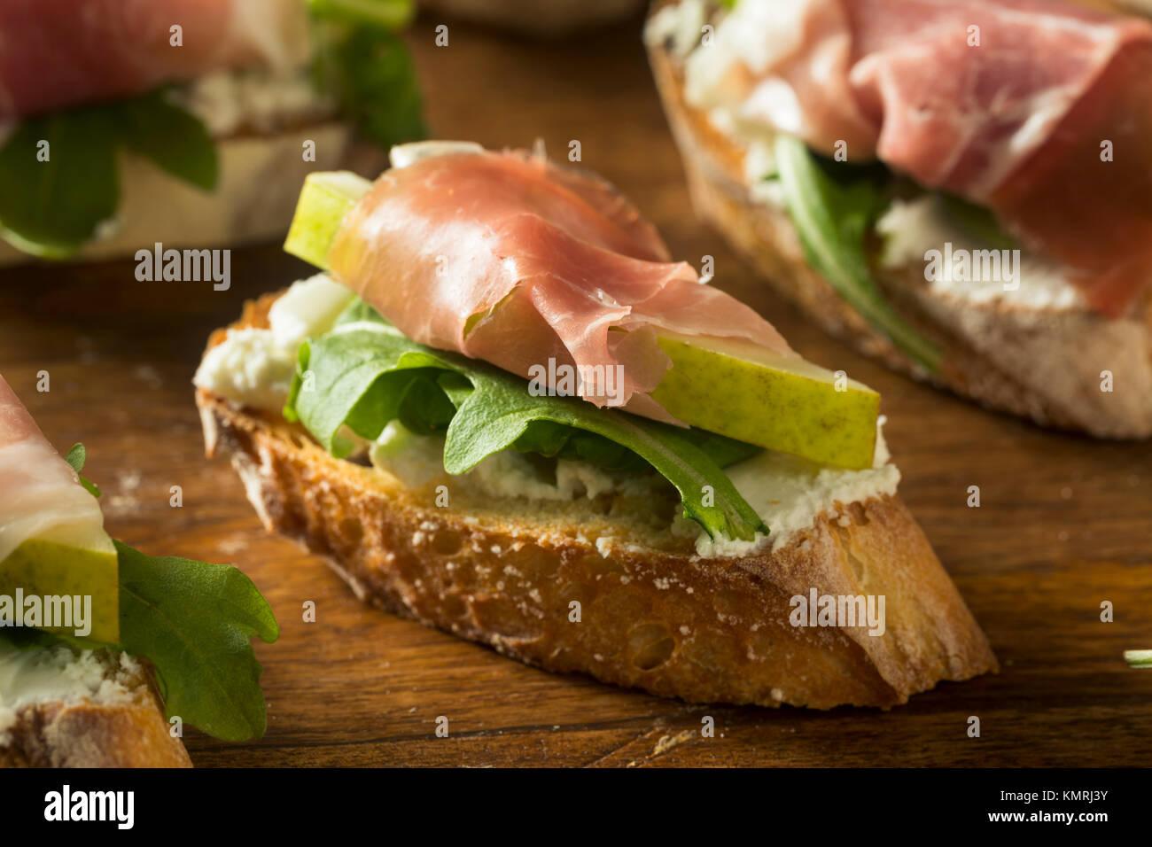Le fromage fait maison Poire Prosciutto Crostini avec Roquette Photo Stock