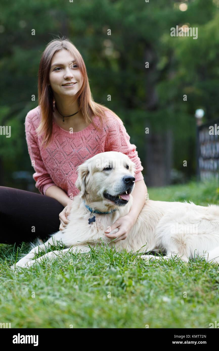 Image de la brunette et dog sitting on lawn Photo Stock
