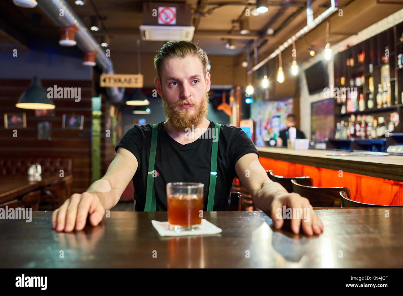 Homme barbu à table dans un pub Photo Stock