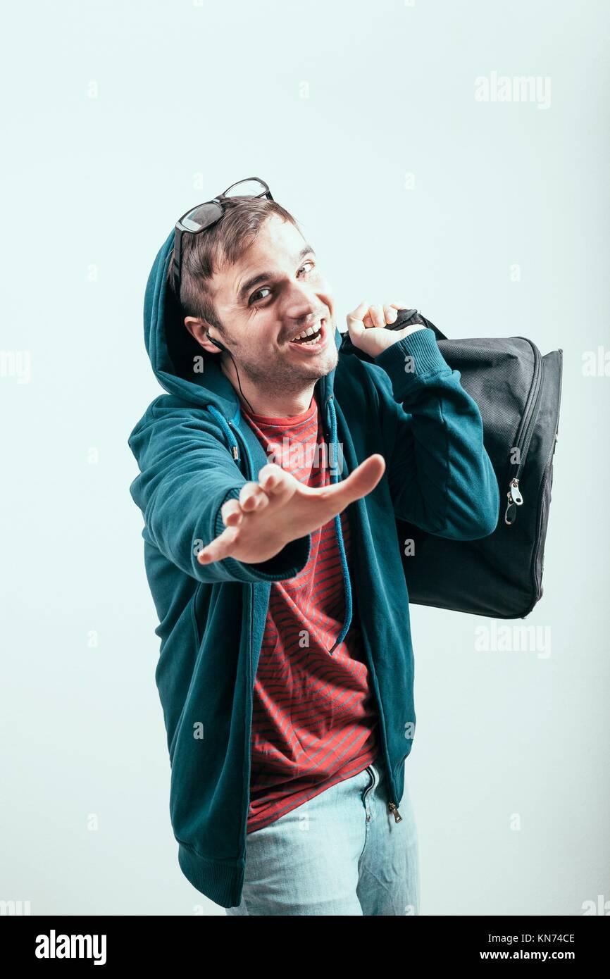 Dans l'homme extatique hoodie voyager avec des bagages. Photo Stock