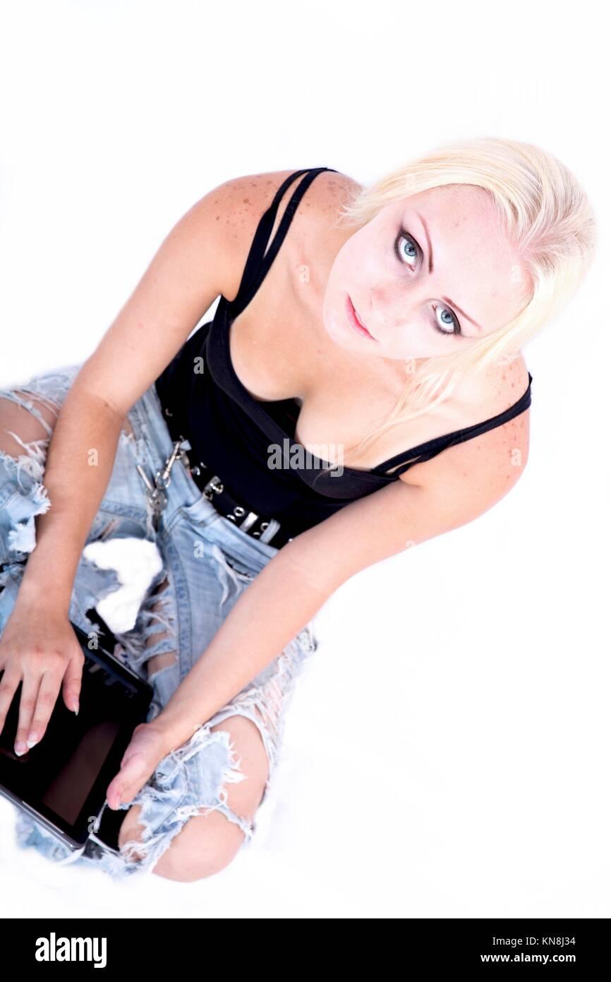Portrait d'une jeune fille blonde d'autres assises sur le sol holding a tablet PC.. Photo Stock