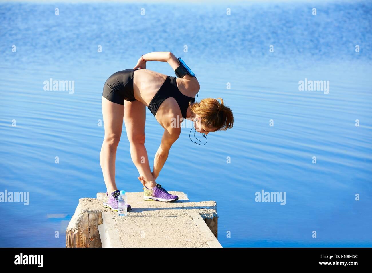 Runner stretching femme dans un lac à l'extérieur de la jetée. Banque D'Images