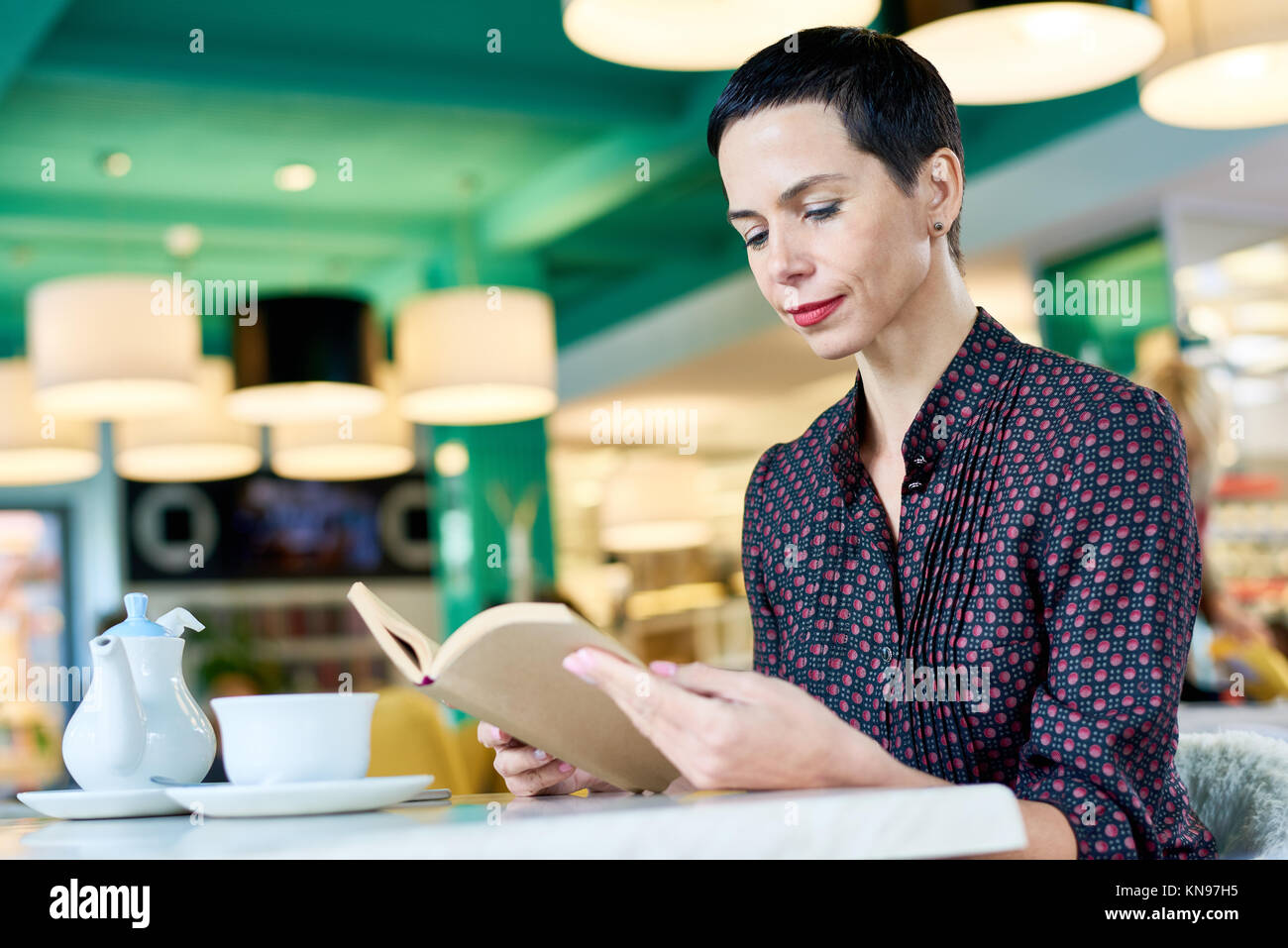 Elegant Woman Reading Book in Cafe Photo Stock