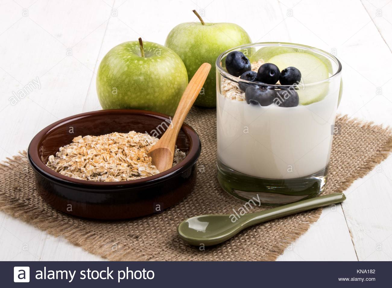 Petit-déjeuner sain avec du yogourt dans un verre vert frais, pommes, bleuets juteux grillées et de l'avoine dans Banque D'Images