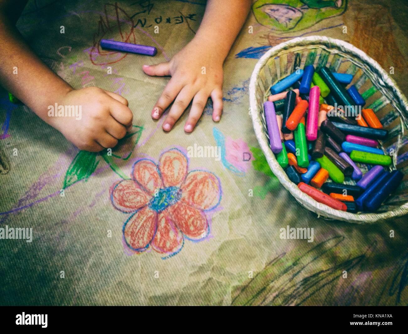 Dessin de l'enfant avec un panier de crayons de cire sur craft papier d'emballage. High angle view. Banque D'Images