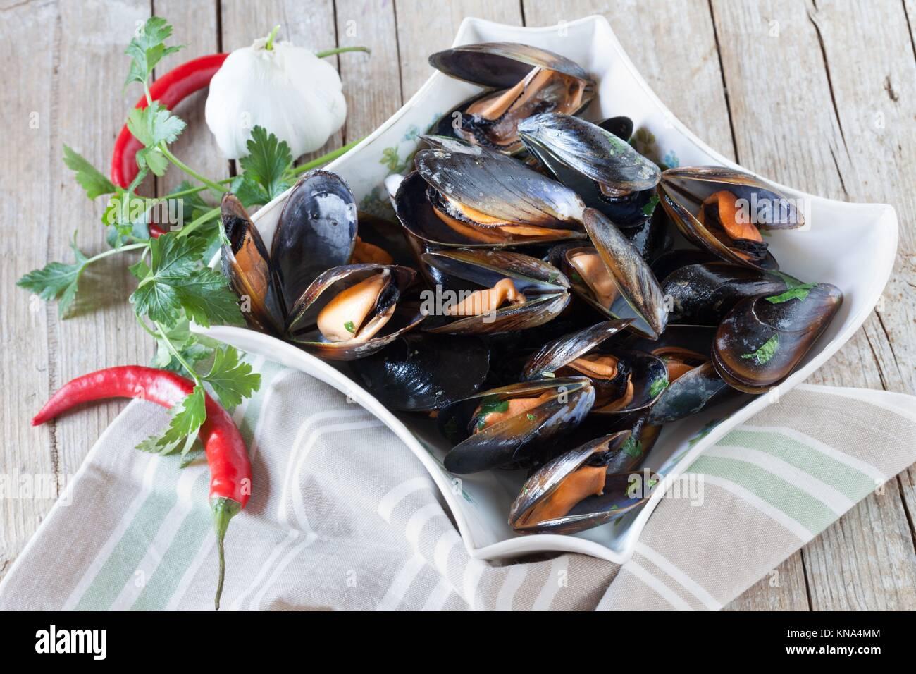 La plaque avec les moules sautées décorées de persil, ail et piment rouge. Photo Stock