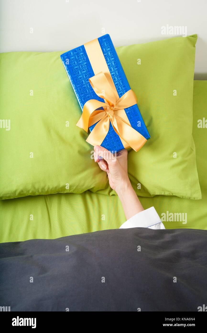 La femme qui sort de feuilles bleu et vert avec enveloppé dans du papier cadeau avec ruban sur l'oreiller. Banque D'Images