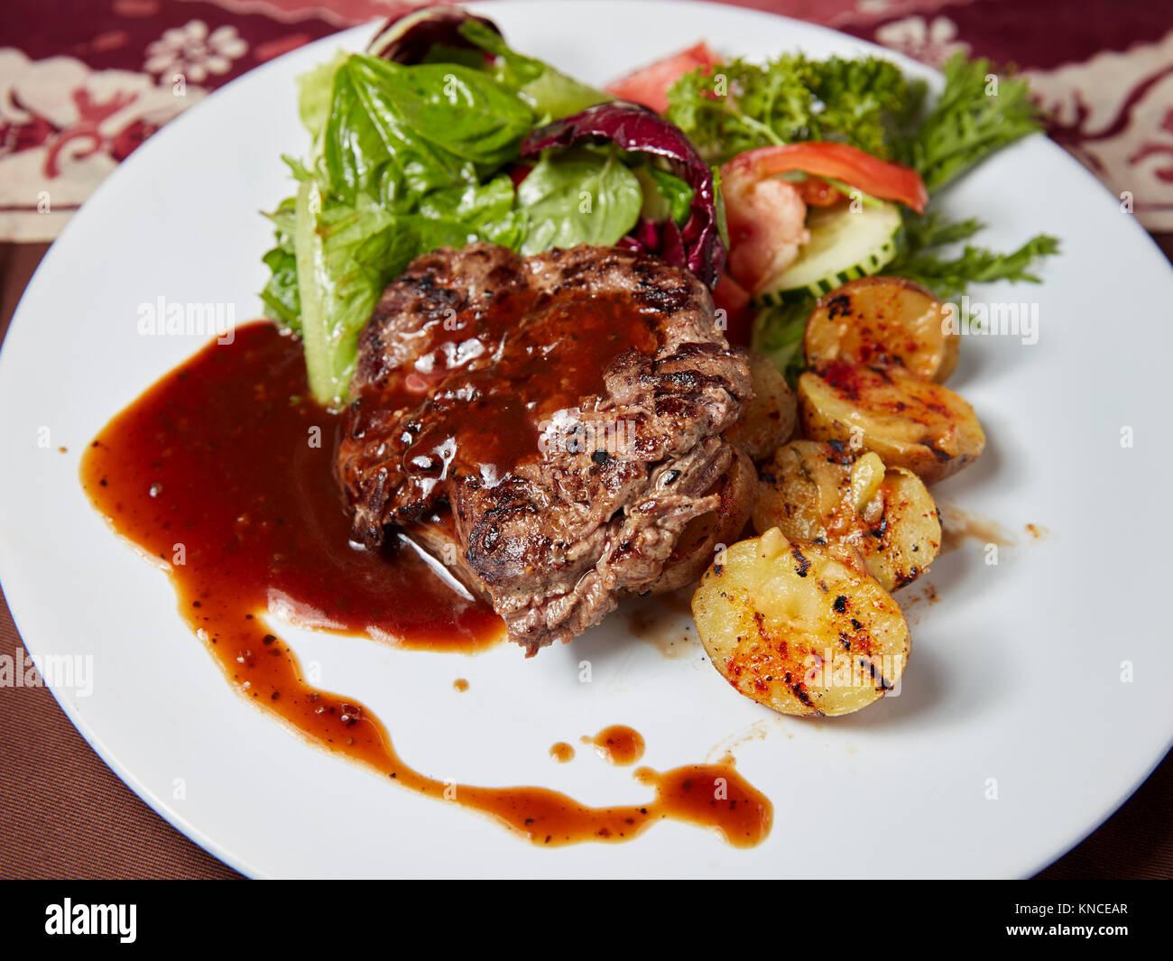 Faux filet de boeuf grillé steak avec les quartiers de pommes de terre et salade verte servi dans un warung Photo Stock