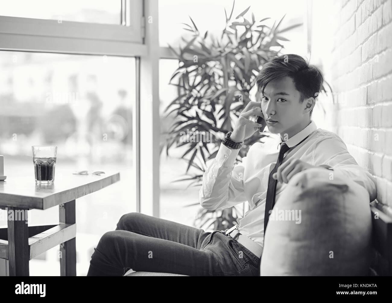 Un jeune homme d'Asie est en attente d'un partenaire dans un café. Bu Photo Stock