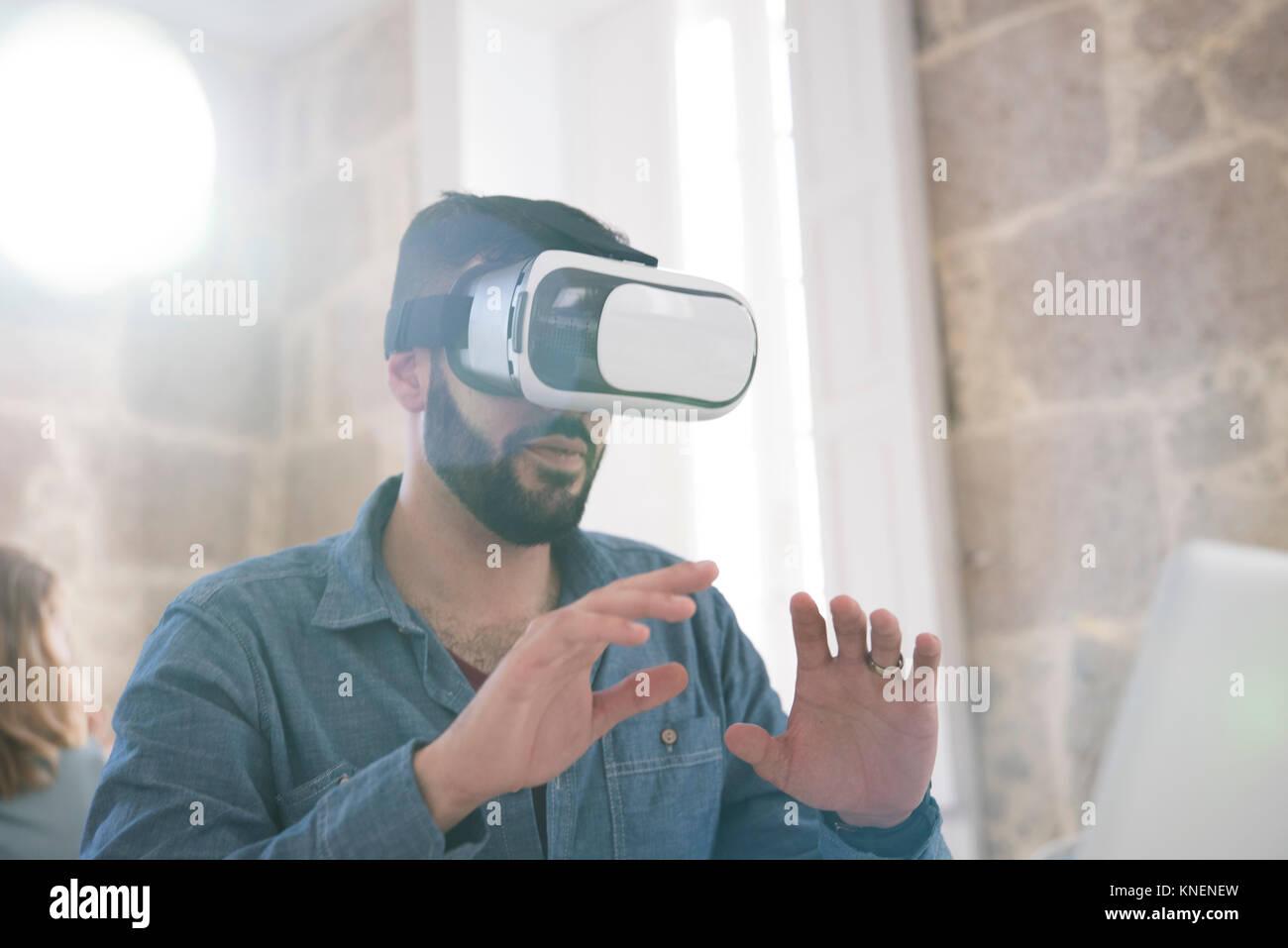 Businessman wearing casque de réalité virtuelle in office Banque D'Images