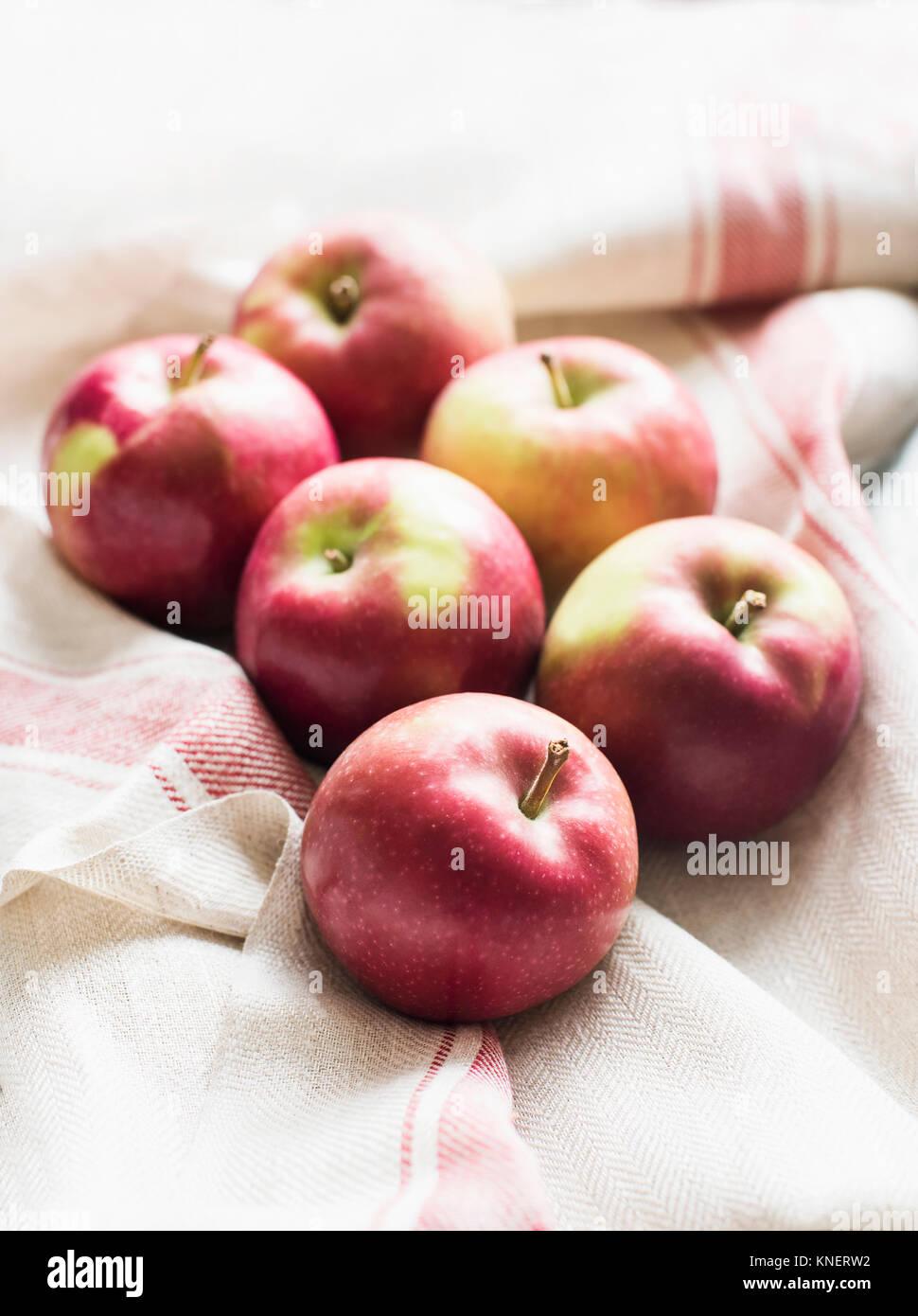 6 pommes rouges sur lin tissu cuisine, close-up Photo Stock