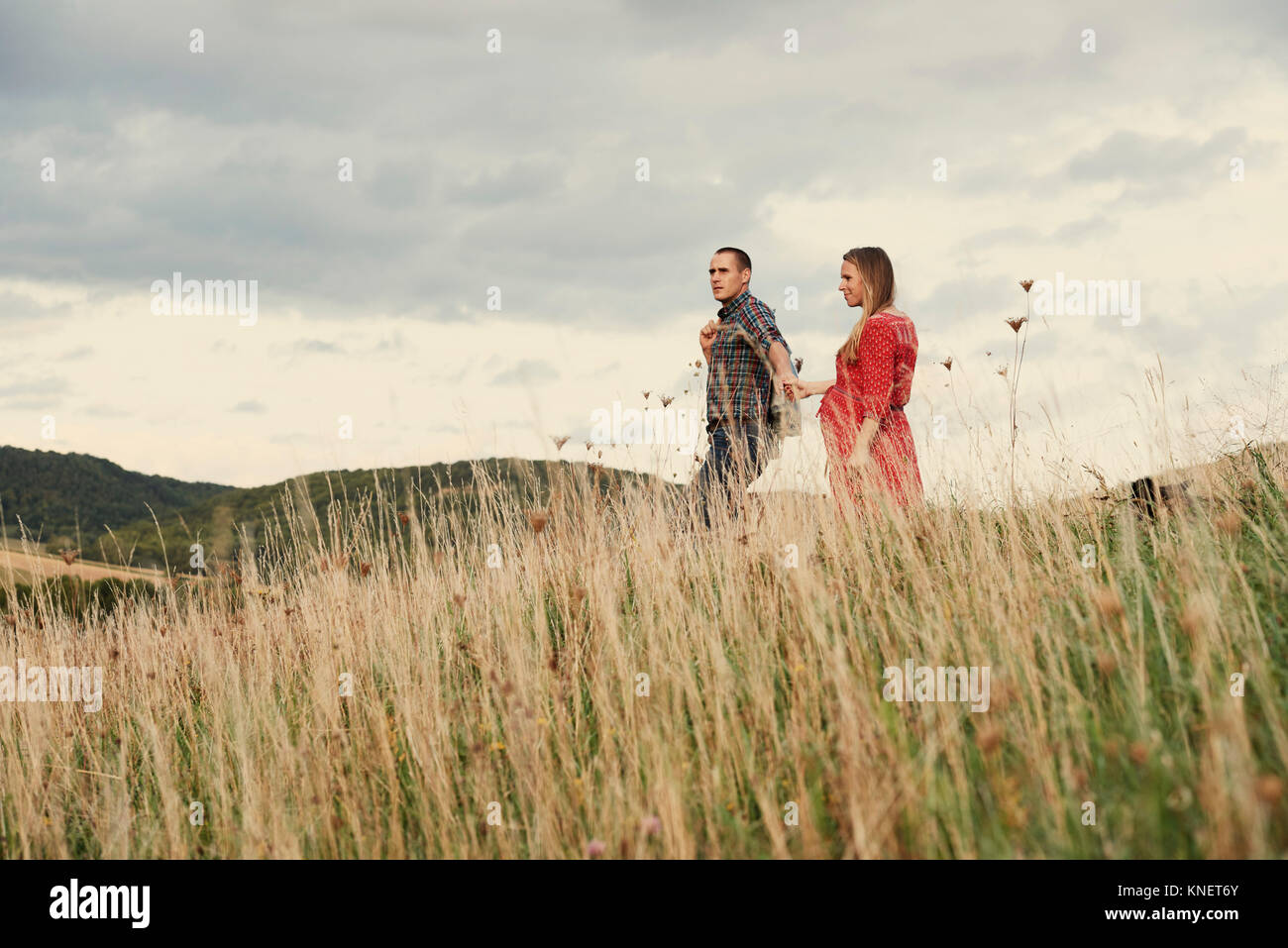 Enceinte Mid adult couple holding hands tout en flânant dans hillside Photo Stock