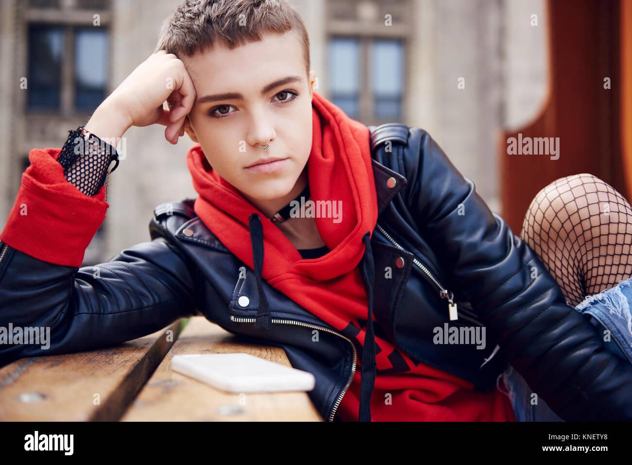 Portrait de jeune femme cool avec les cheveux courts au banc de la ville Photo Stock