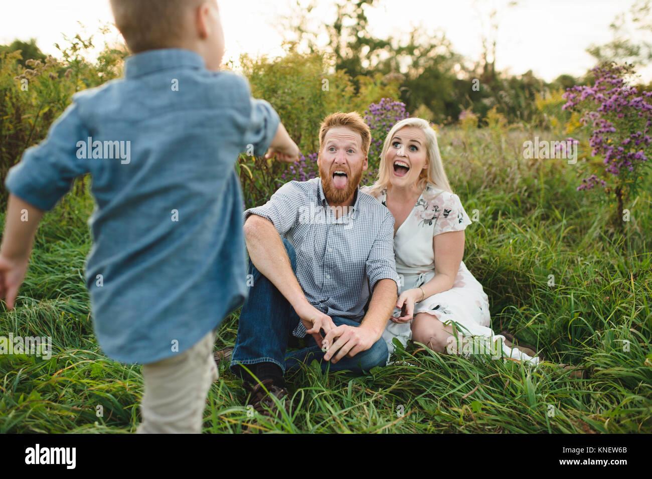 Garçon surprenant parents assis dans l'herbe haute Photo Stock