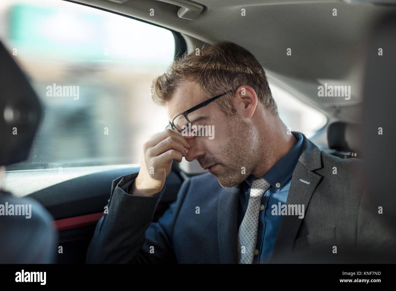 Portrait en arrière de voiture, se frottant les yeux fatigués Photo Stock