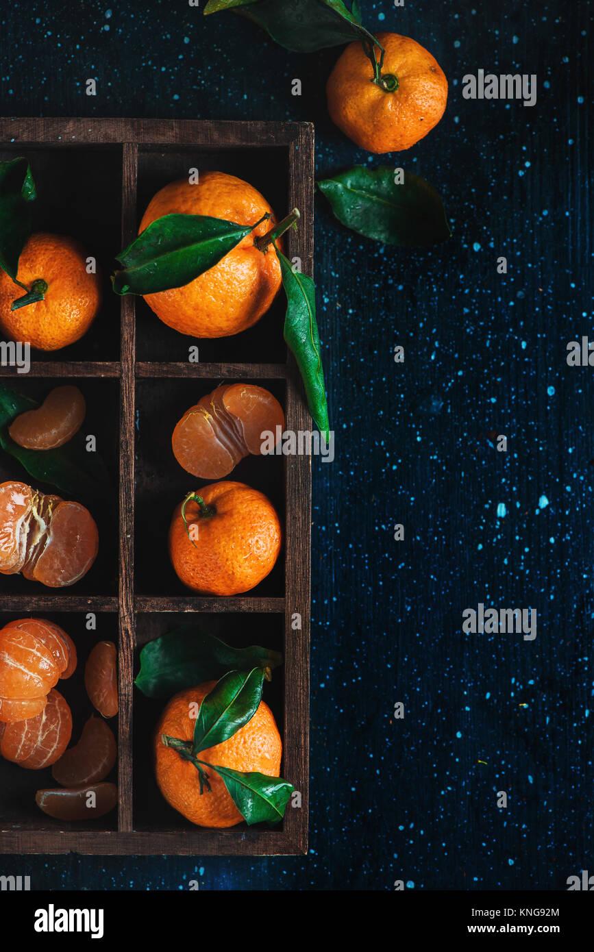 Mandarines dans une caisse de bois sur un fond sombre. Un assortiment de clémentines avec des feuilles vertes. Photo Stock