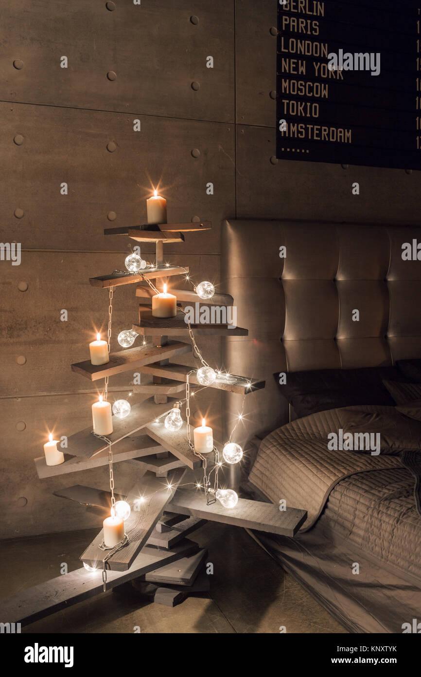 Arbre de Noël en bois de remplacement. Un arbre de Noël fait main et ampoule électrique sur le plancher Photo Stock