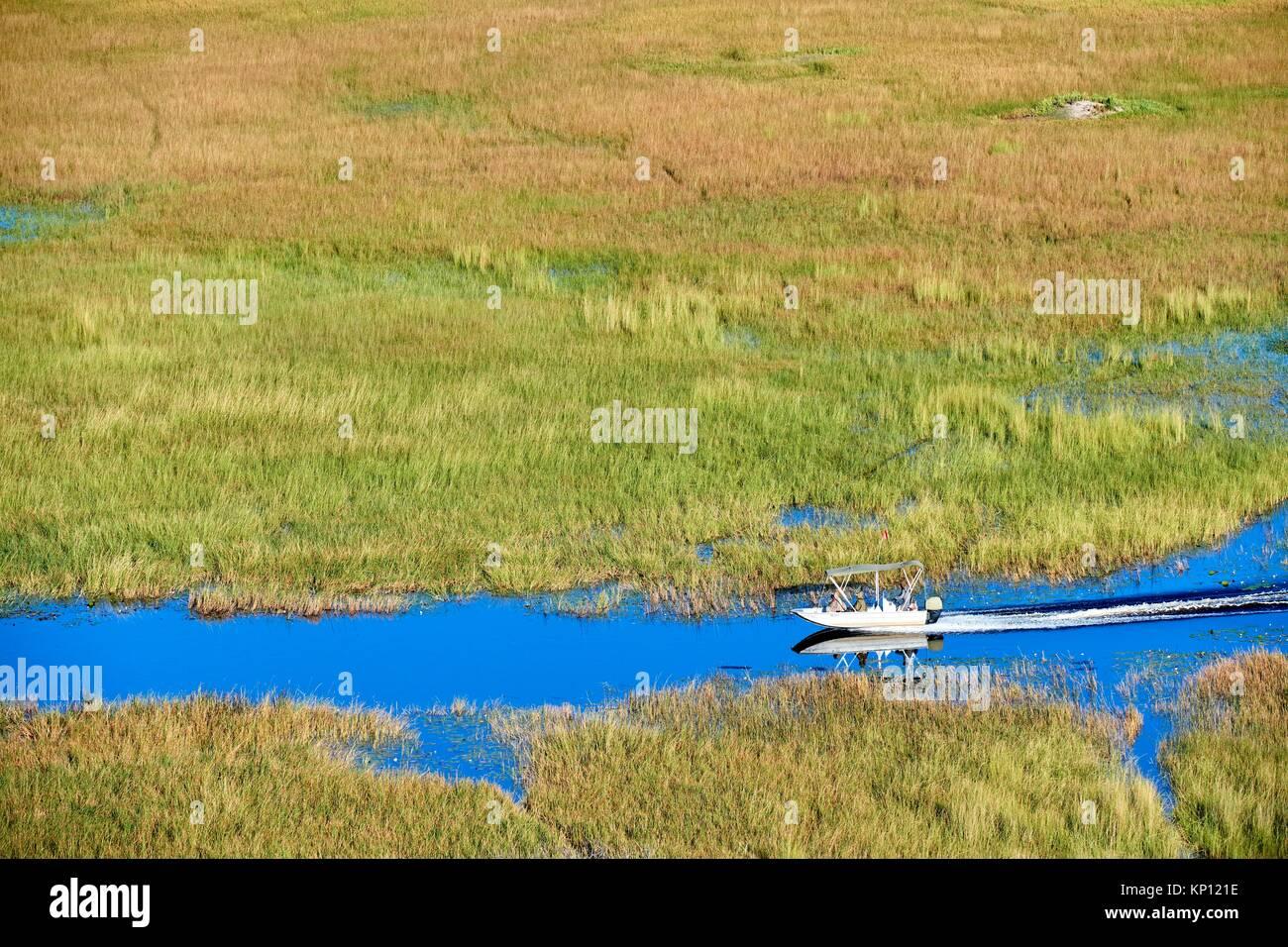 Vue aérienne de la croisière en bateau sur un canal du delta de l'Okavango, au Botswana. Photo Stock