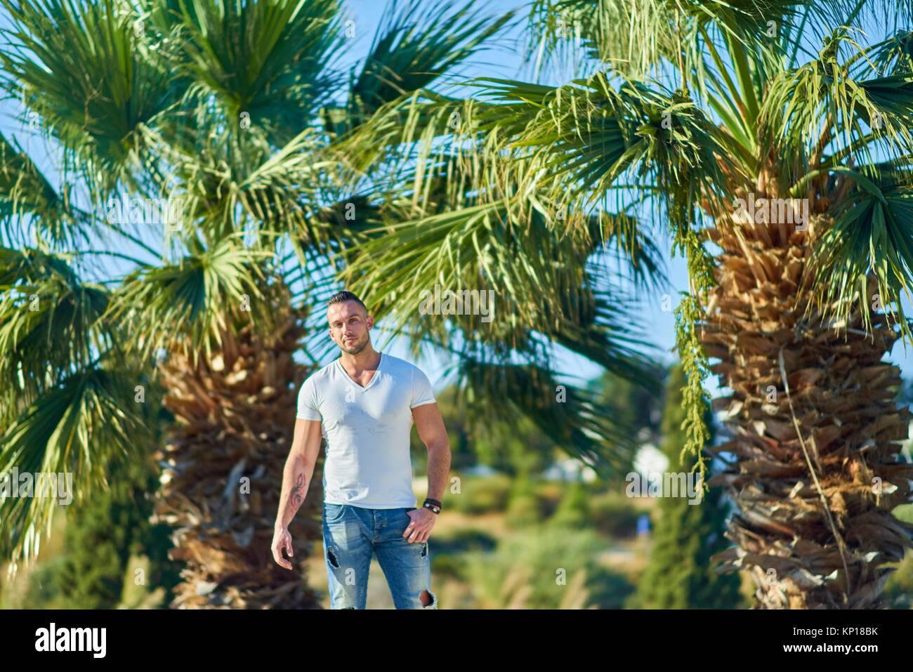 Certain homme musclé entre les palmiers. La moitié grec et moitié anglais à l'origine ethnique. Photo Stock