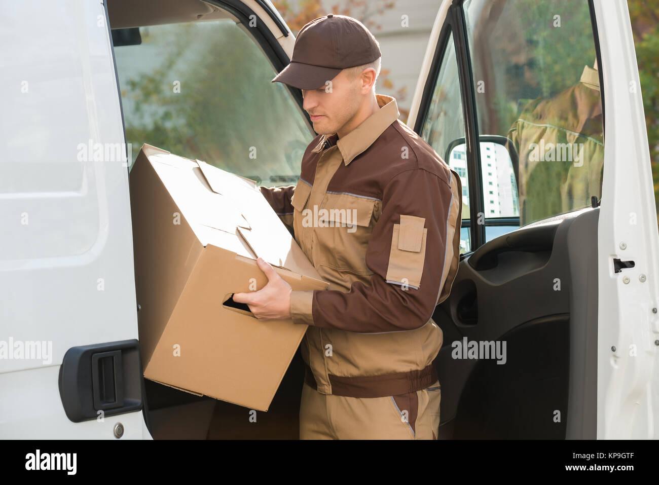 L'homme dépose de boîte en carton de livraison d'un camion Photo Stock