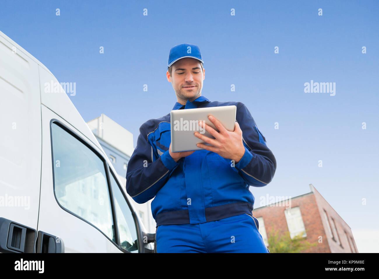 Delivery Man Using Digital Tablet par camion contre le ciel Photo Stock
