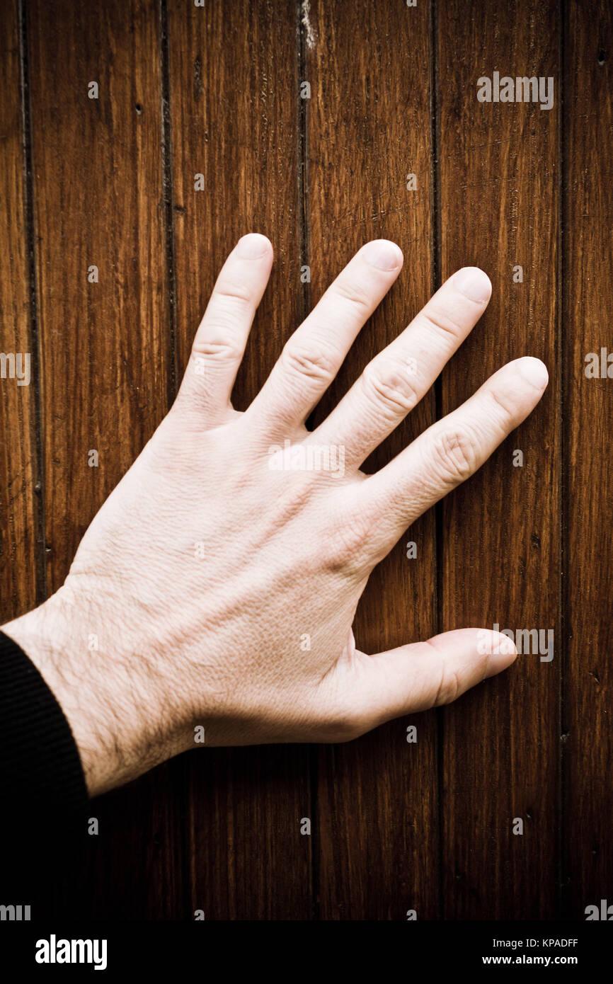 La main des hommes touchant une surface en bois, concept pour le sens du toucher Photo Stock