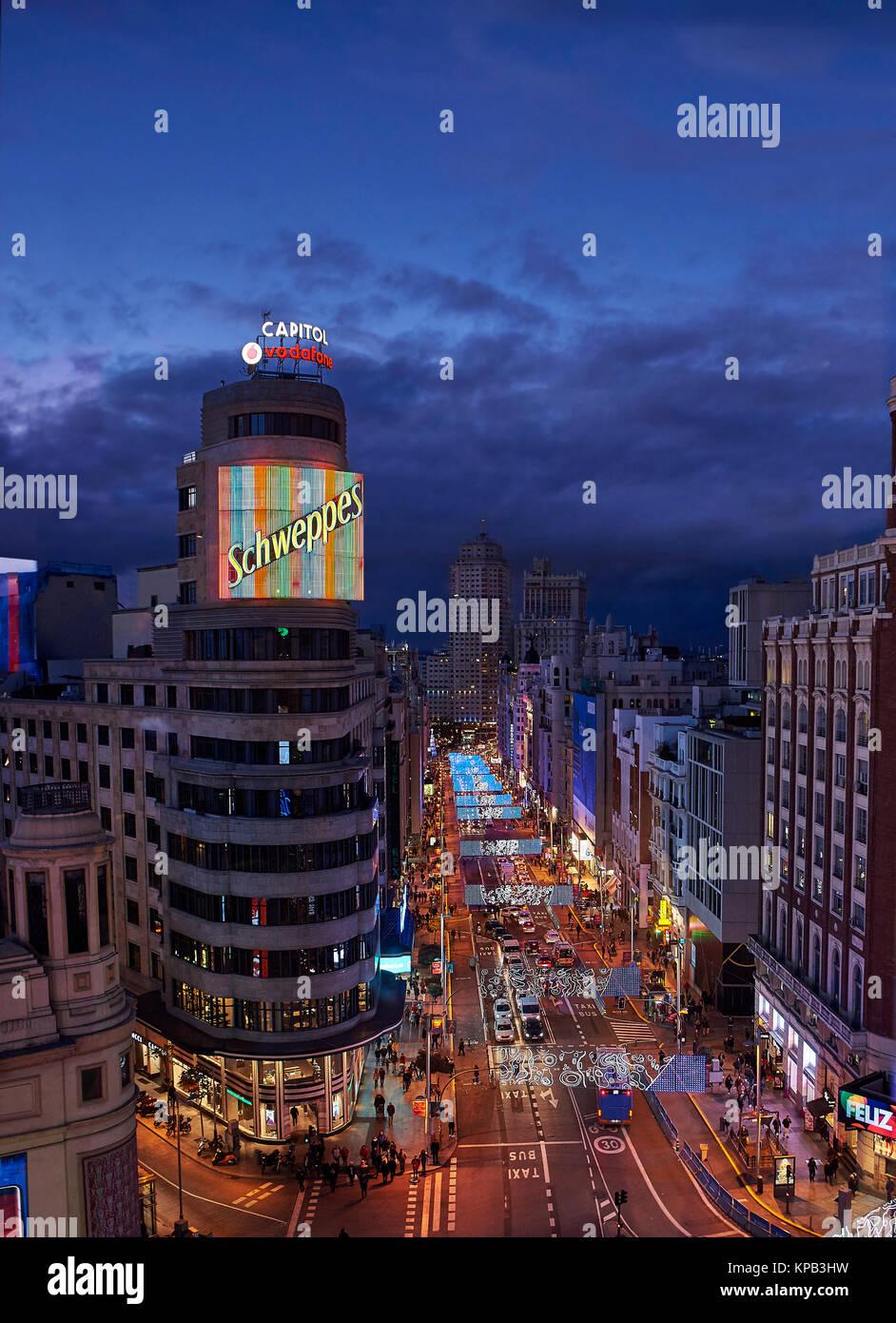 La tombée de la vue sur la rue Gran Via éclairé par les lumières de Noël et enseignes néon Photo Stock