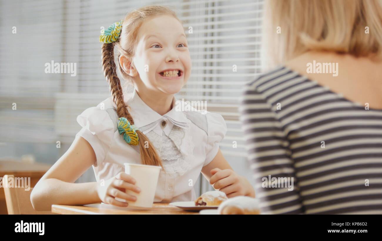 Mère et fille sont assis dans un café, manger émotionnellement parlant sweetsand Photo Stock