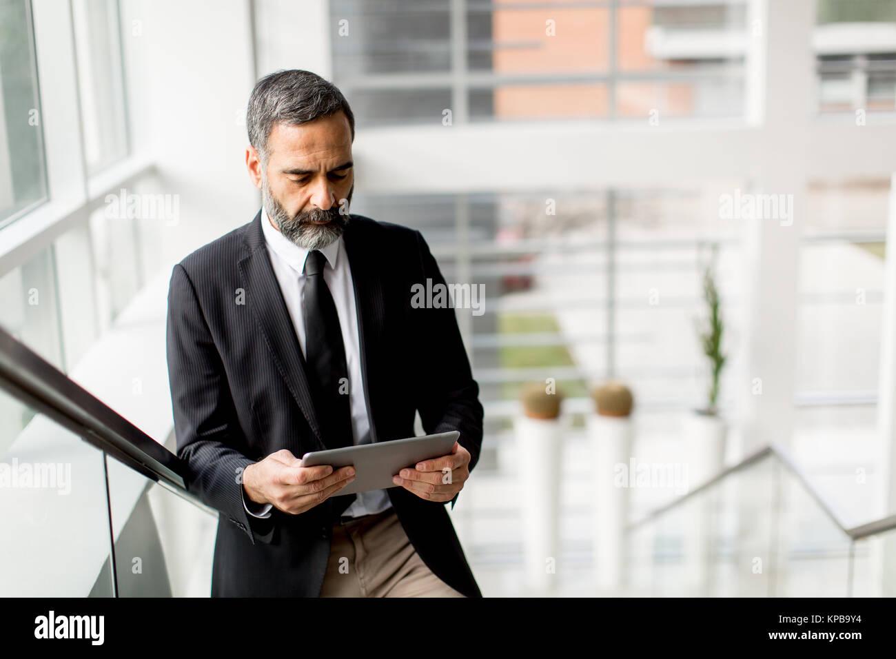 Beau moyen age businessman with digital tablet in l'office modren Photo Stock