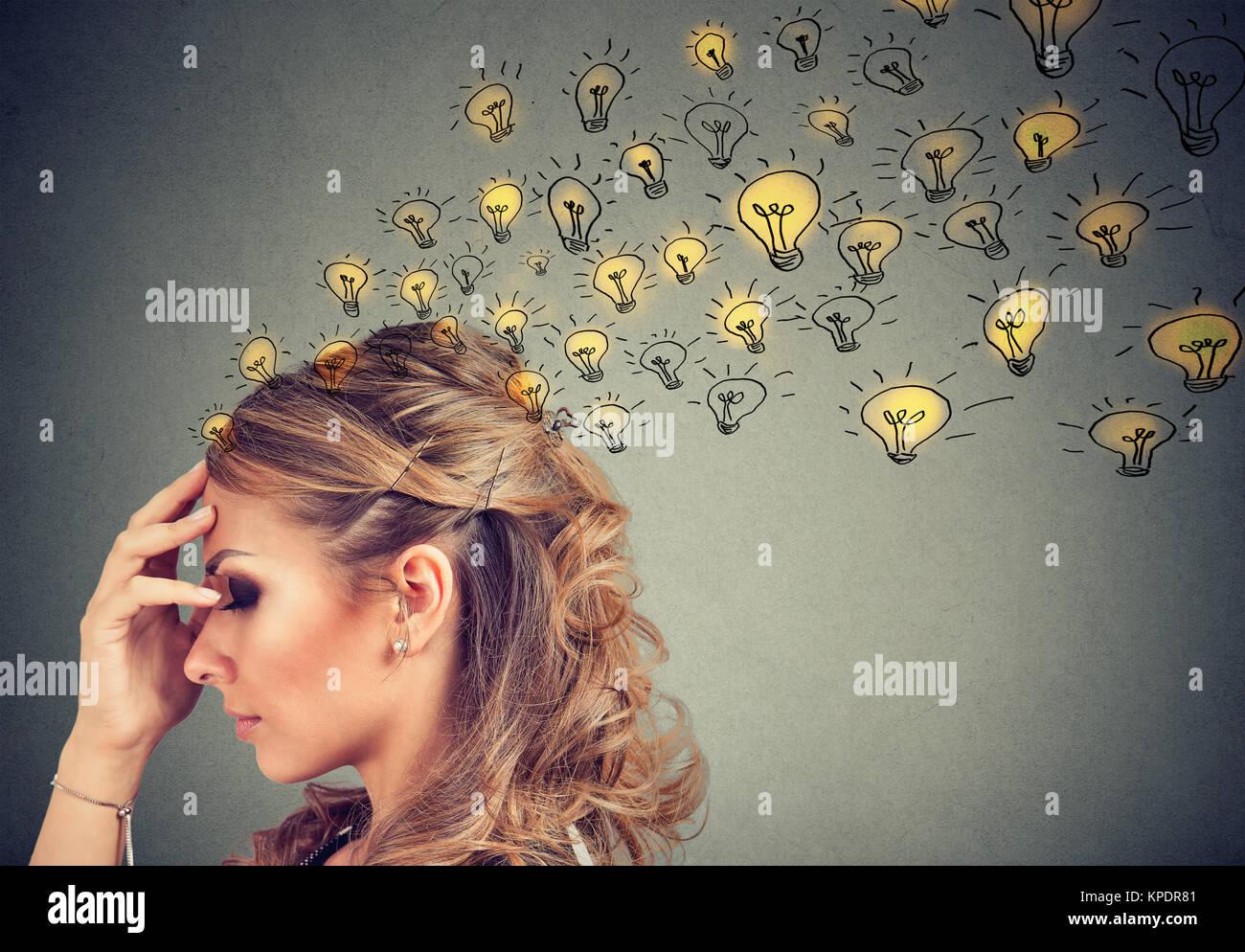 Jeune femme pense avoir concentré avec beaucoup d'idées avec gravure en toile de ampoules. Photo Stock