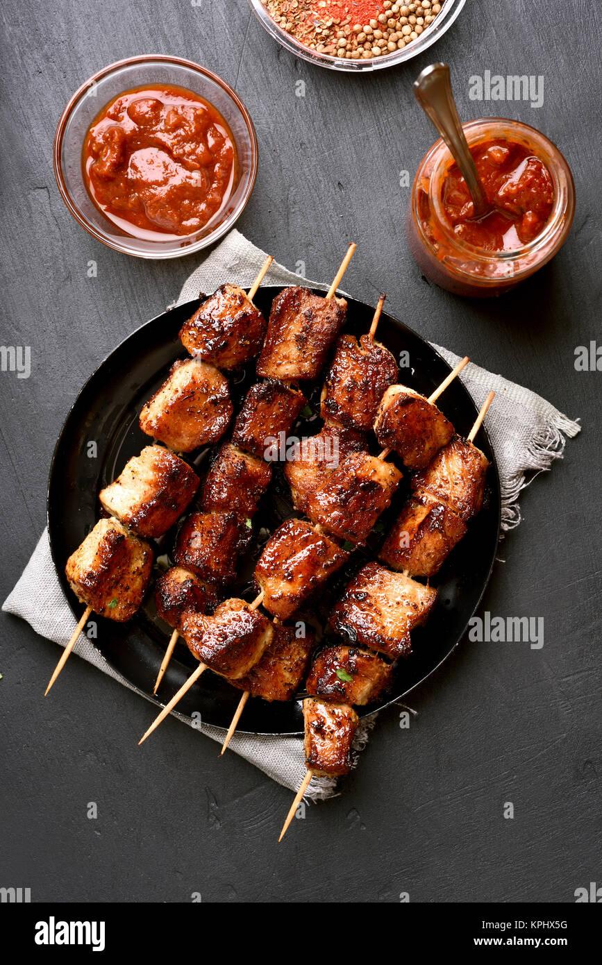 Des brochettes de porc grillé sur fond noir. Vue de dessus, de l'alimentation mise à plat Photo Stock
