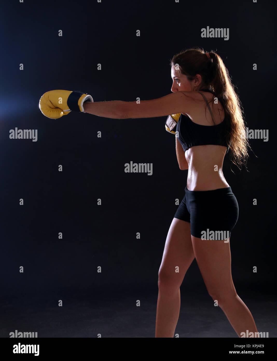 Boxer. Femme Fitness portant des gants de boxe jaune Photo Stock