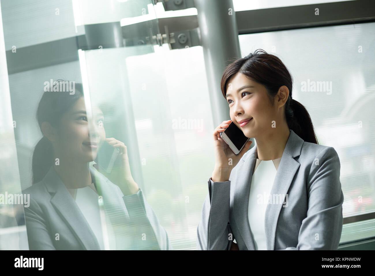 Businesswoman parler à l'intérieur de cellulaire office Photo Stock