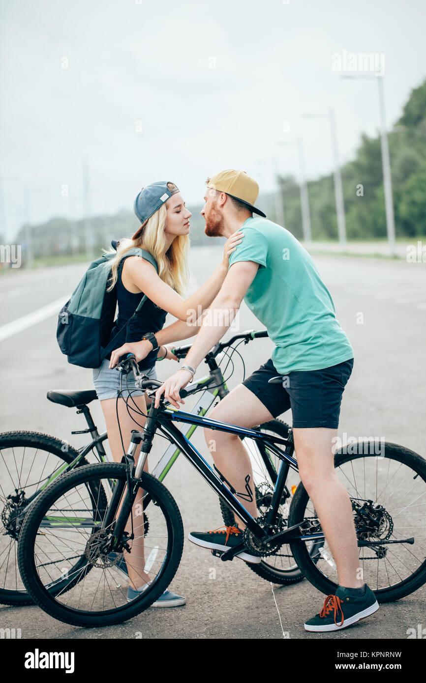 Sports romantique couple kissing contre l'arrière-plan flou avec des bicyclettes Photo Stock