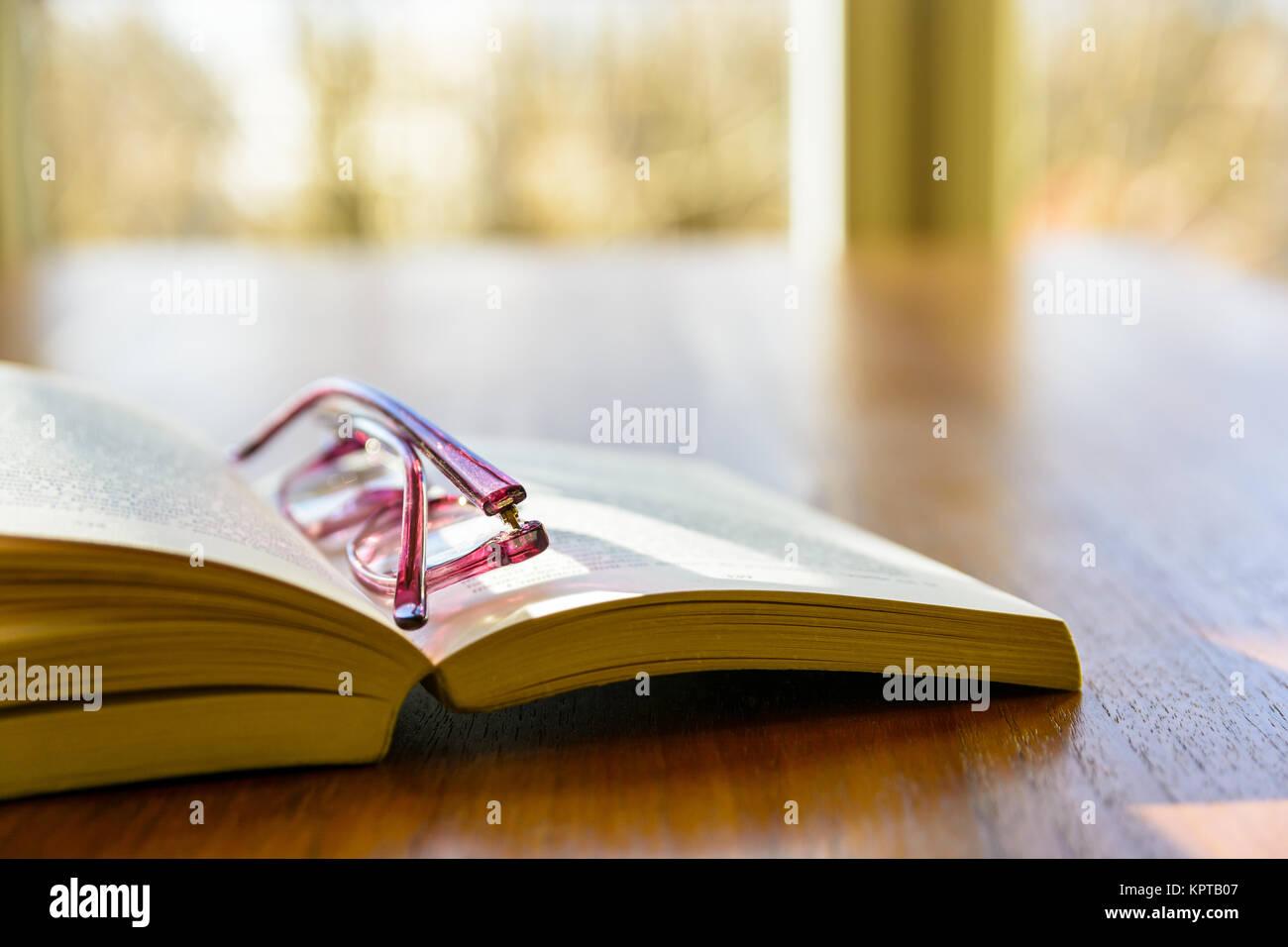 Vue rapprochée d'un livre de poche avec une paire de lunettes de lecture sur elle, posant à plat sur Photo Stock