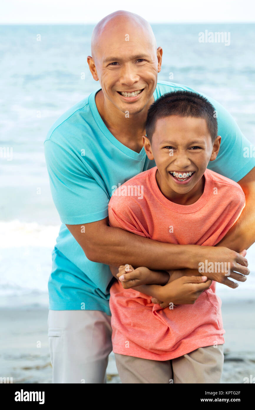 Père jouant avec ses enfants sur la plage. Photo Stock