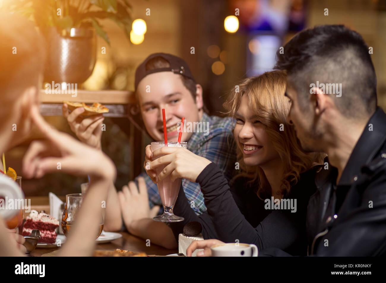 Les amis en buvant un café ensemble. Les femmes et l'homme au café, parler, rire Photo Stock