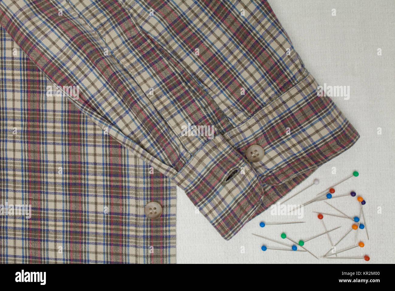 Brassard d'une chemise à carreaux et de broches sur un tableau du tailleur, copiez l'espace, Photo Stock