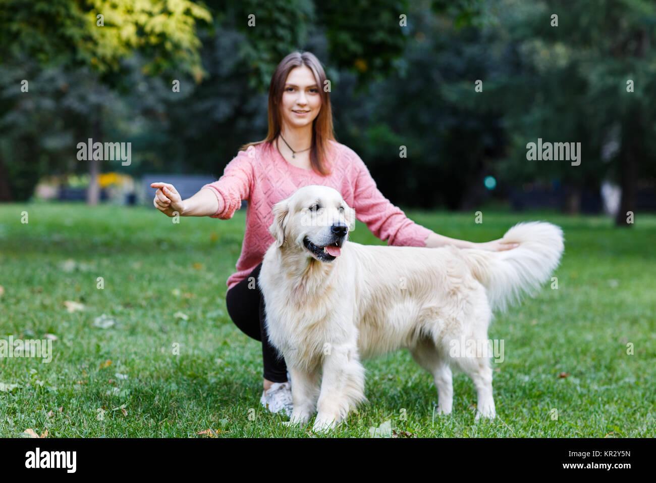 Image de brunette avec chien sur pelouse verte Photo Stock