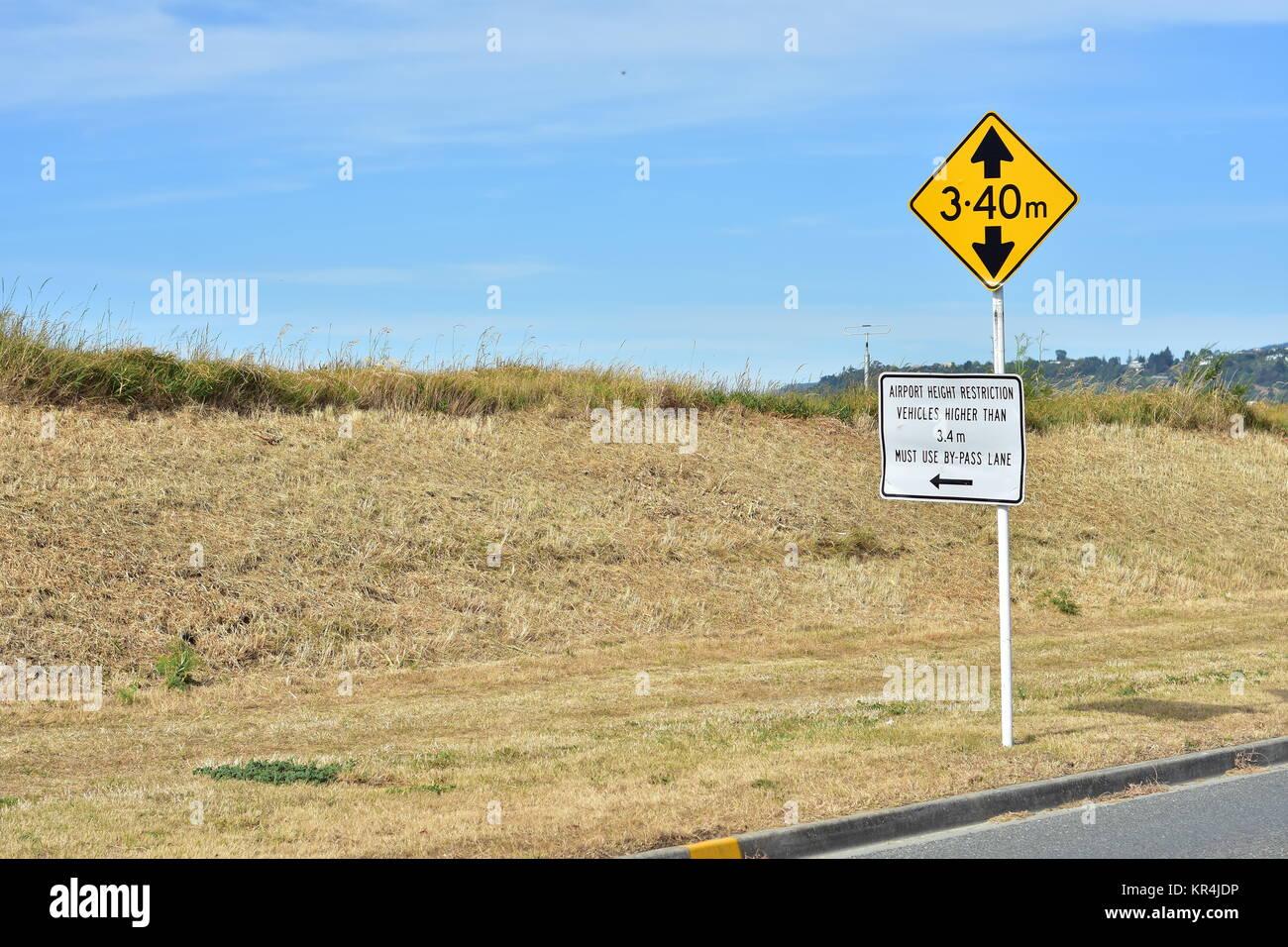 Limitation de hauteur rectangulaire jaune vif signe avec bold bloc noir lettres sur poteau de métal blanc. Photo Stock