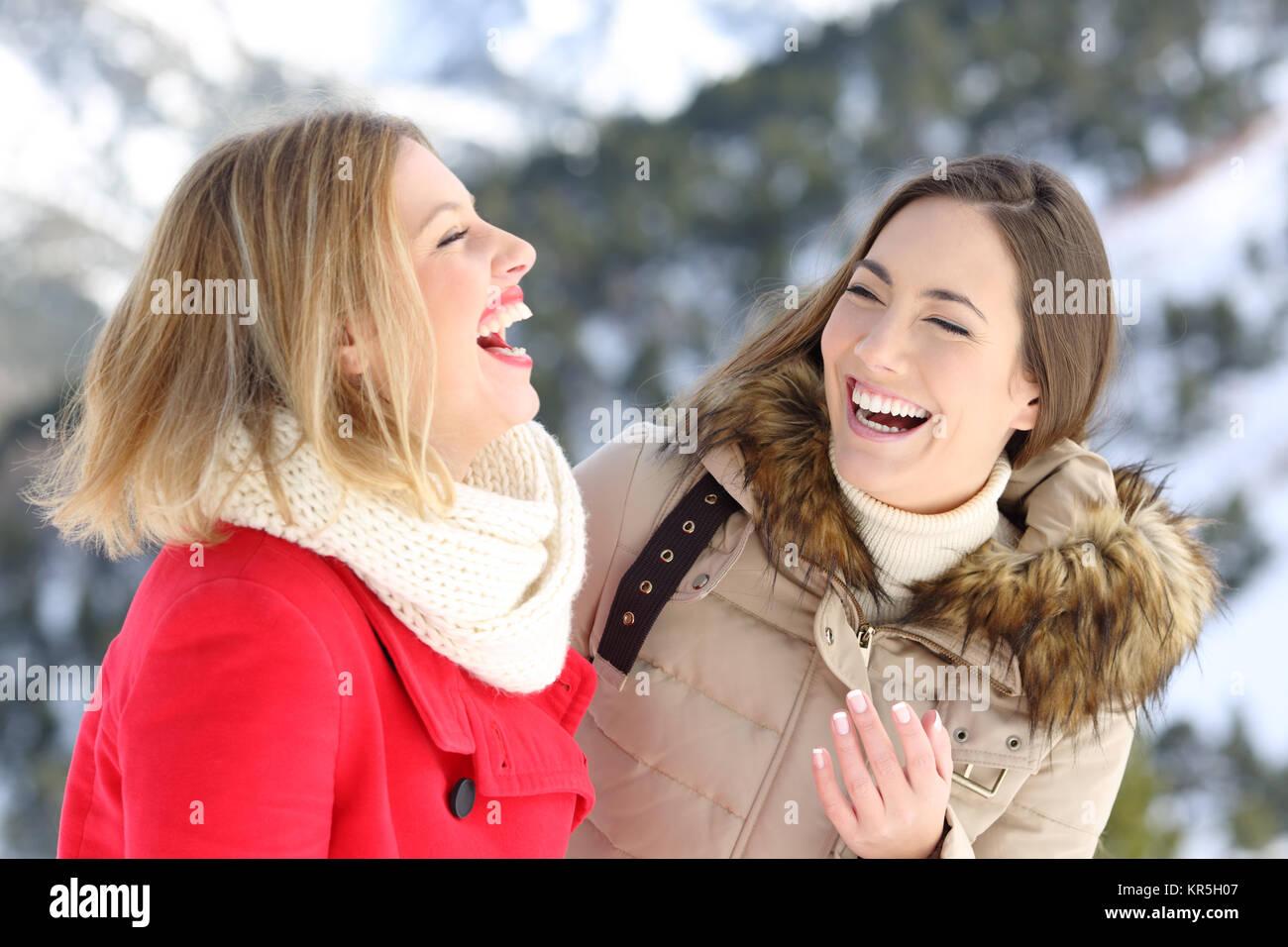 Heureux deux amis qui rient fort profitant de vacances d'hiver dans la montagne enneigée Photo Stock