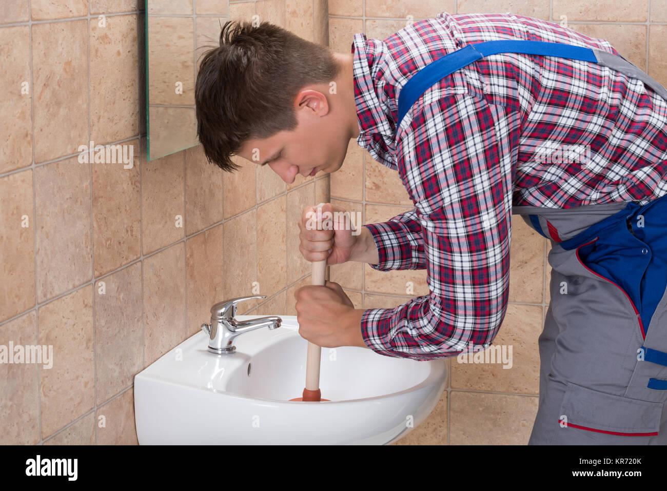 L'aide plombier plongeur dans salle de bain évier Photo Stock
