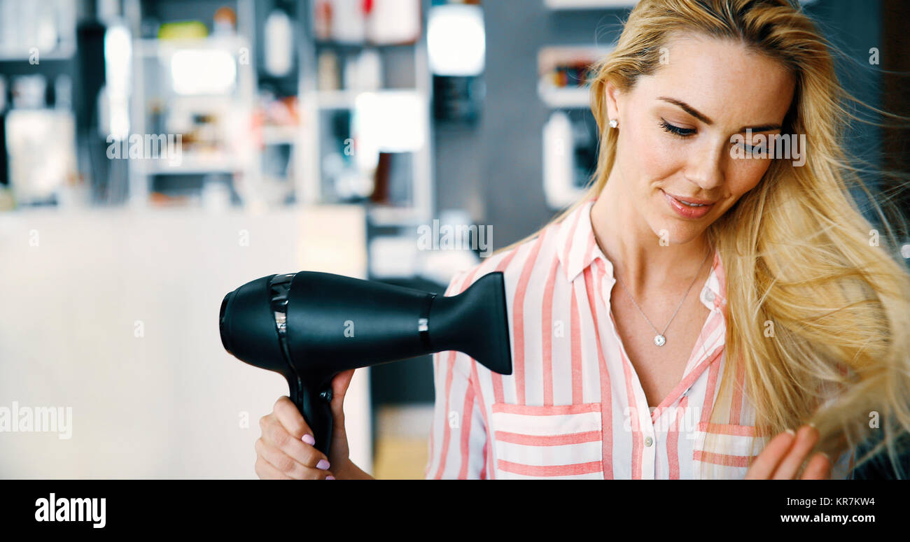 Smiling young woman blow drying hair Photo Stock